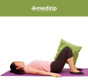 mujer aplastando una almohada colocada entre ambas rodillas