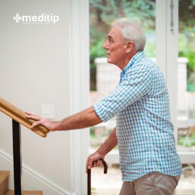 Persona de la tercera edad con dificultad para subir escaleras debido a dolor por bursitis