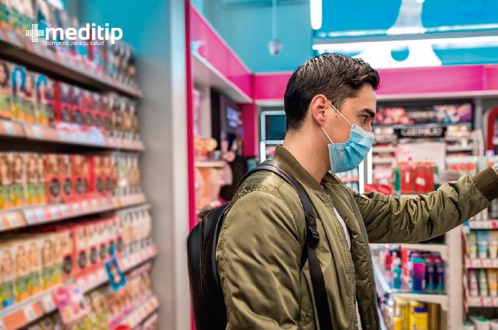 Hombre usando cubrebocas en el supermercado: uso correcto de cubrebocas y respiradores N95