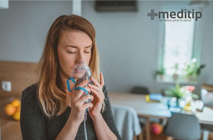 Mujer con máscara de oxígeno: síntomas respiratorios por exposición a niveles altos de partículas PM2.5