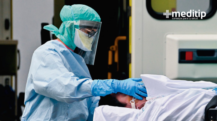 Profesional de la salud con equipo de protección personal y paciente Covid