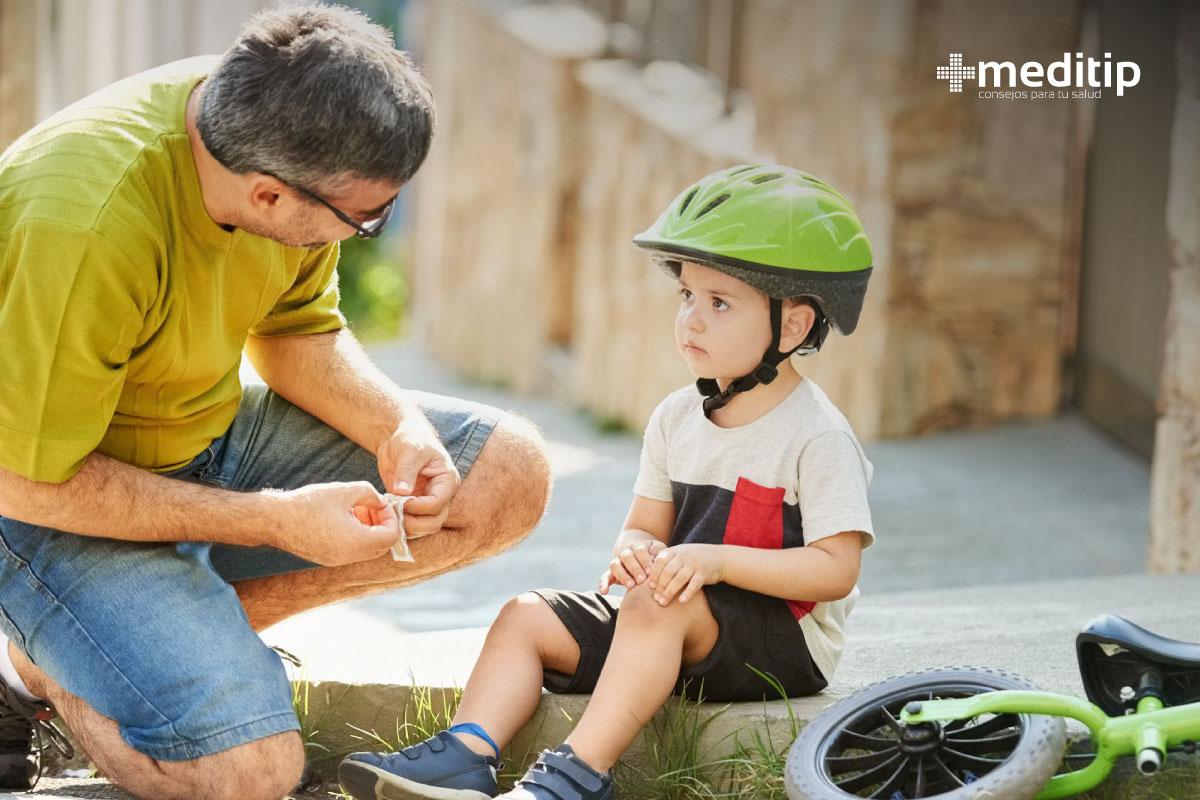Papá e hijo: niño con herida en la rodilla debido a un accidente en bicicleta